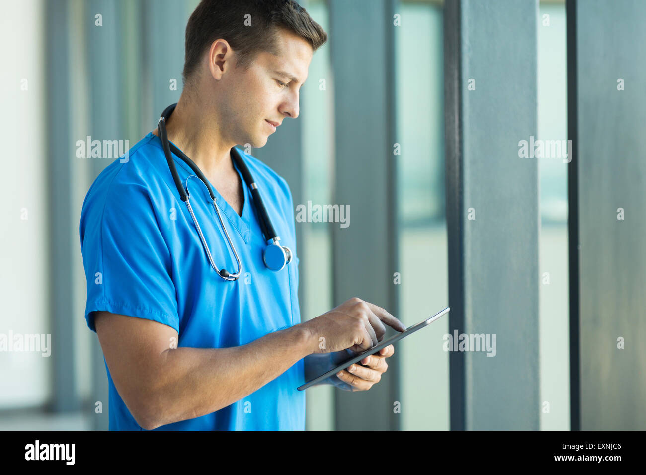 good looking young health care worker using tablet pc - Stock Image