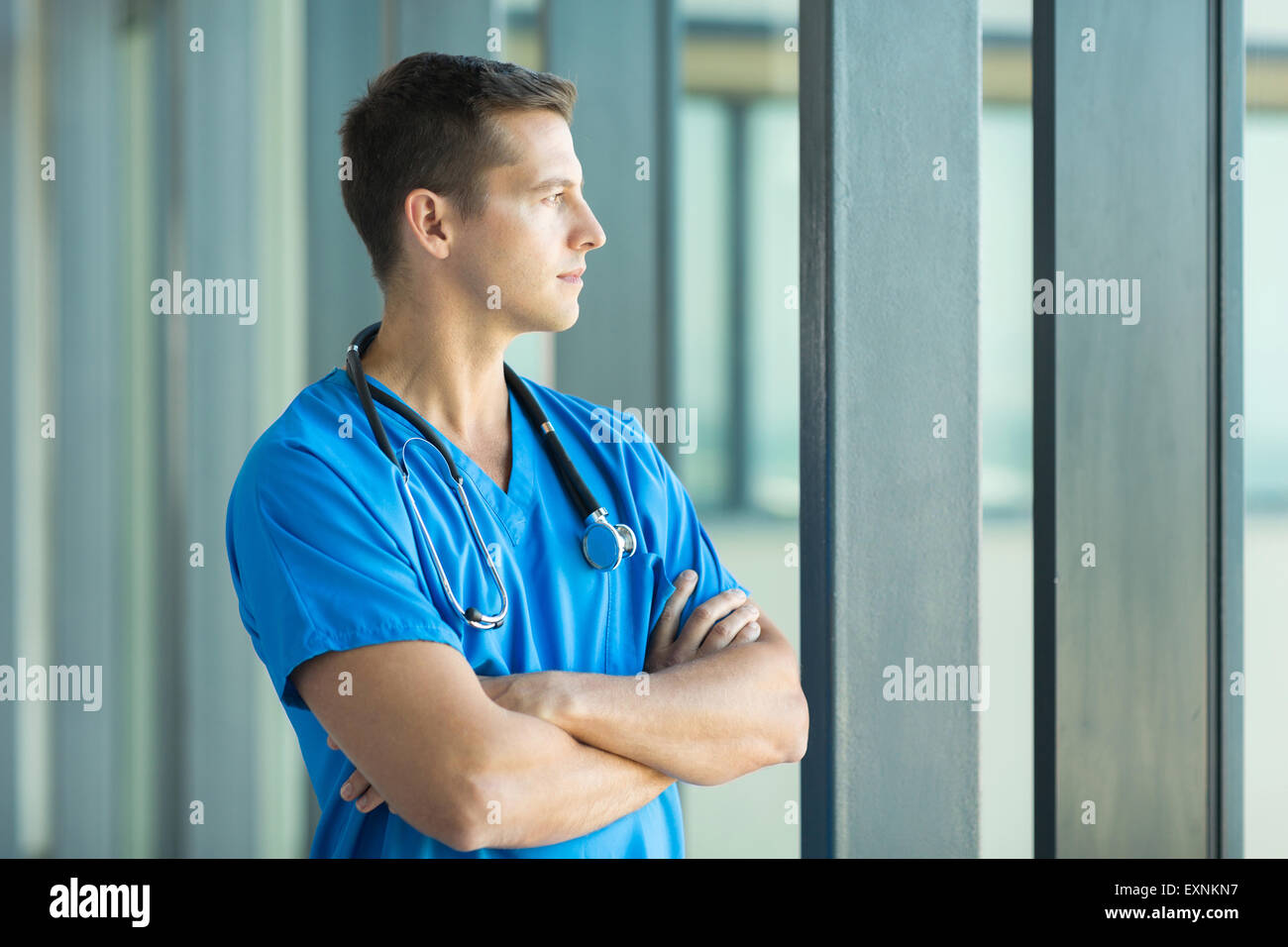 thoughtful doctor looking through office window - Stock Image