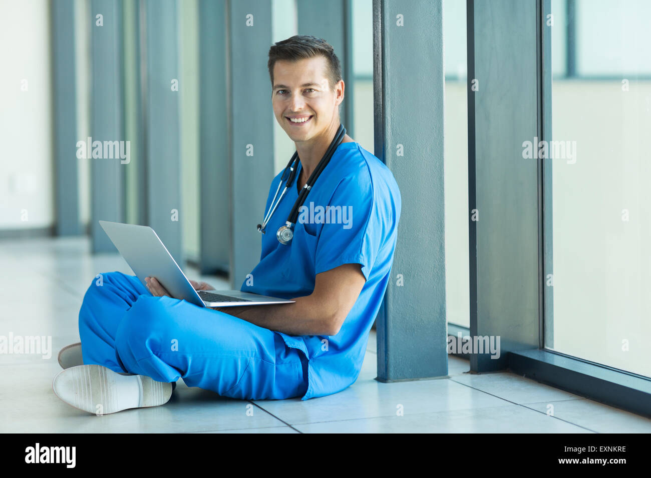 medical worker sitting on hospital floor and using laptop computer - Stock Image