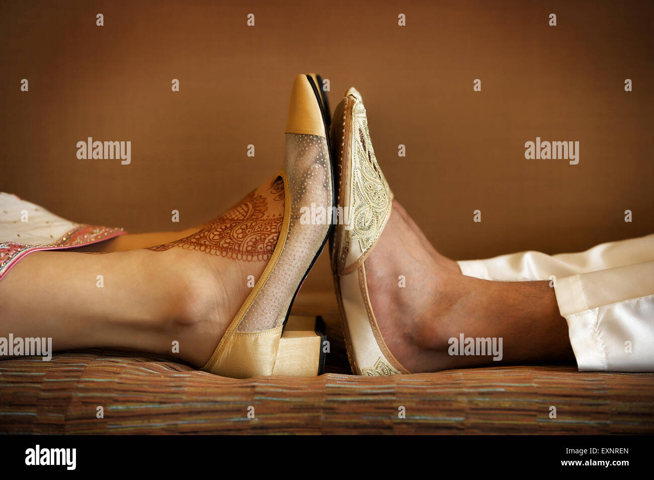 Image of Indian bride and groom's wedding shoes with feet touching - Stock Image