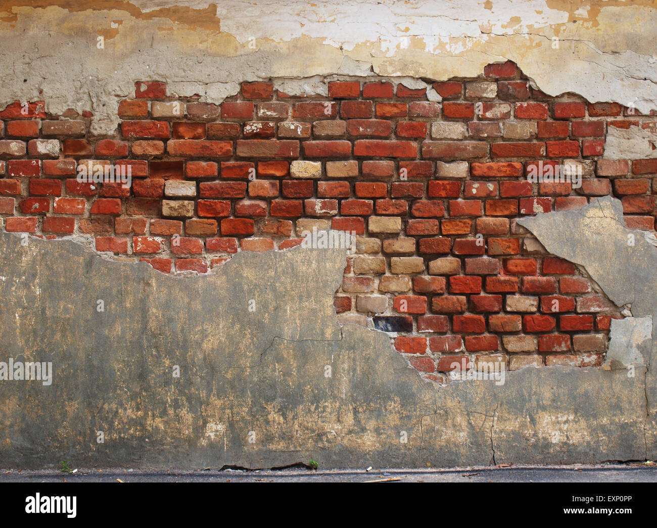 Stone wall of the old brick, decorated with destroyed obsolete plaster Stock Photo