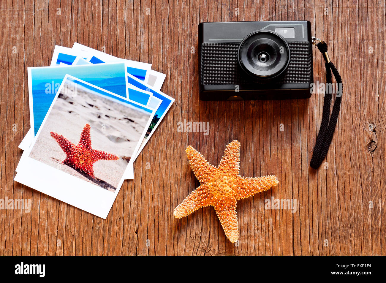 high-angle shot of a retro camera, a starfish and some photos, shot by myself, of beach scenes, placed on a rustic - Stock Image