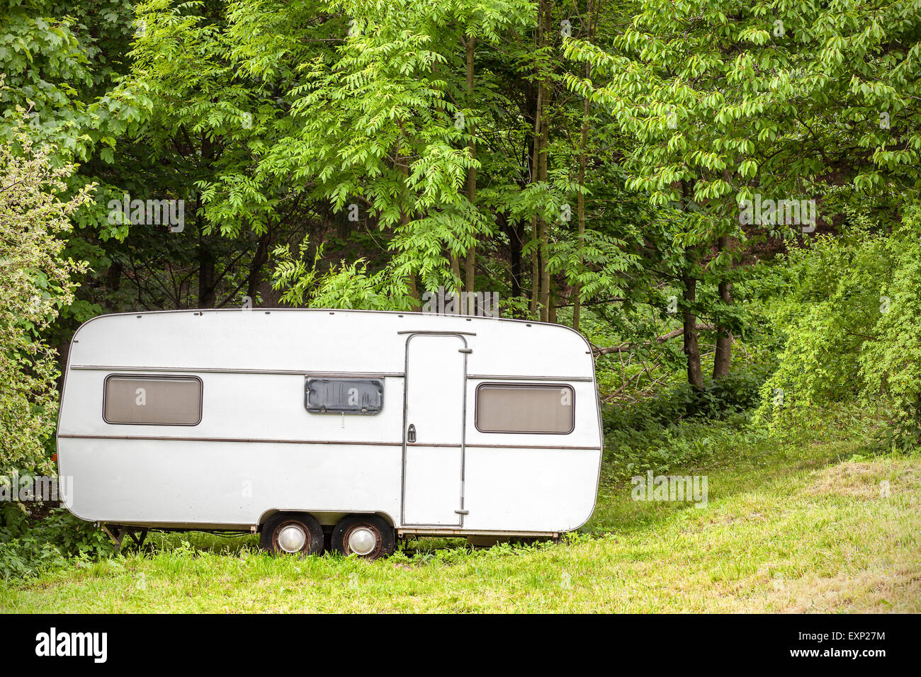 Old camping trailer standing in woods on summer day, nature holiday concept. - Stock Image