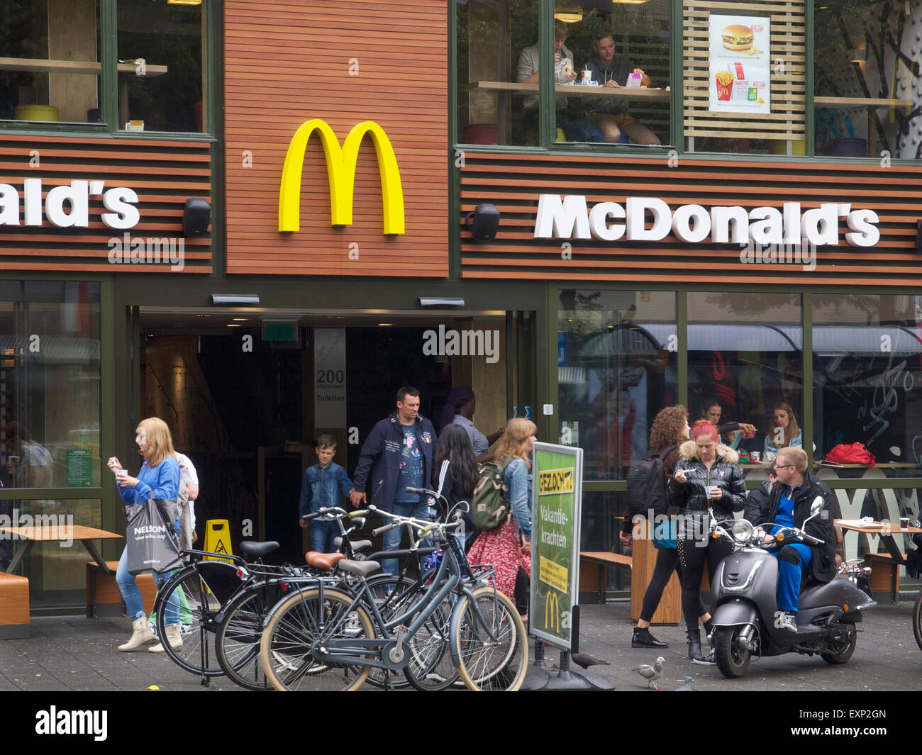 Mc Donalds fast food restaurant Breda city centre the Netherlands with many people - Stock Image
