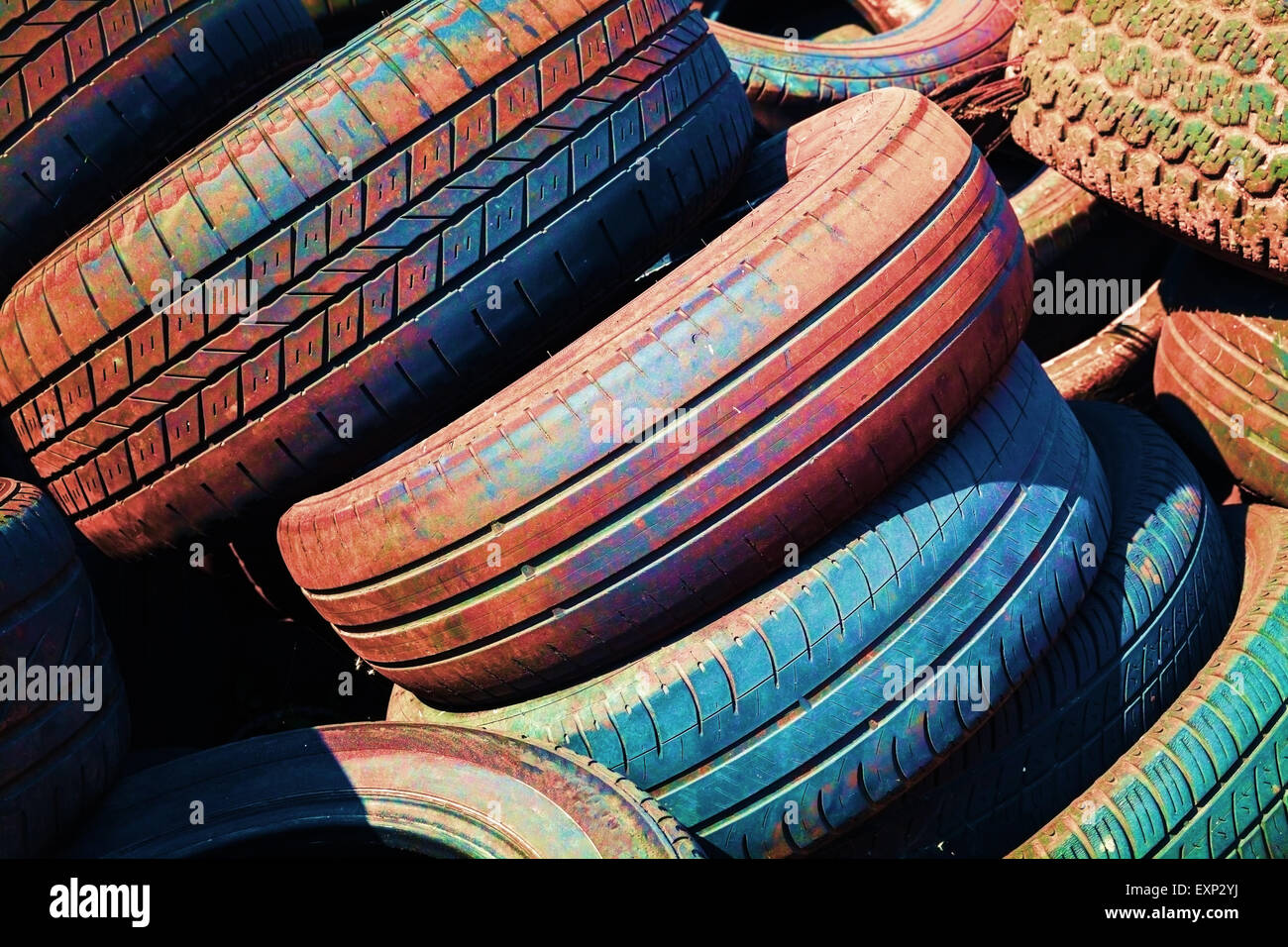 Heap of old colorful worn-out automotive tires - Stock Image