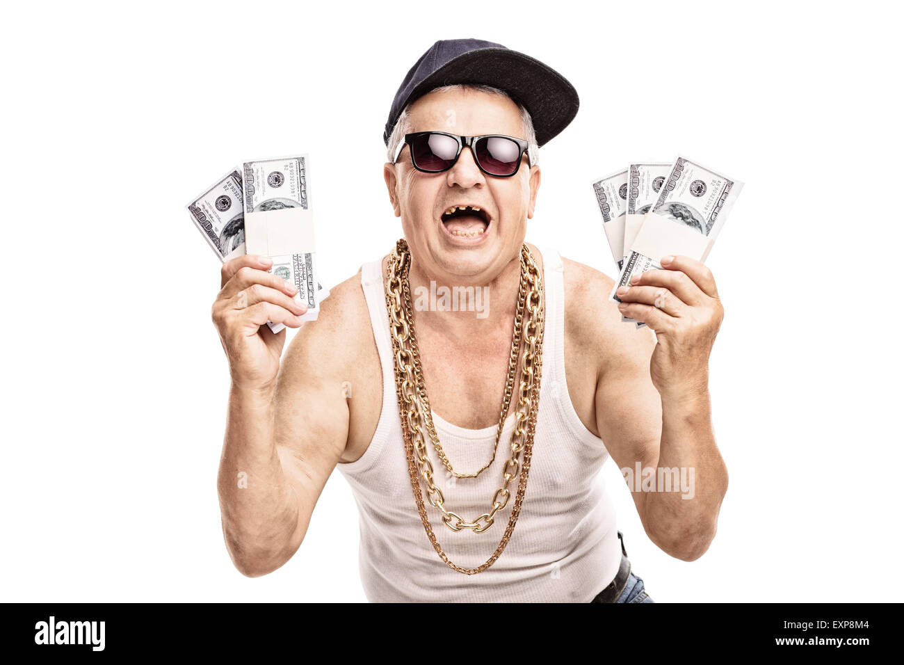 Delighted senior in hip hop outfit holding a few stacks of money and looking at the camera isolated on white background - Stock Image