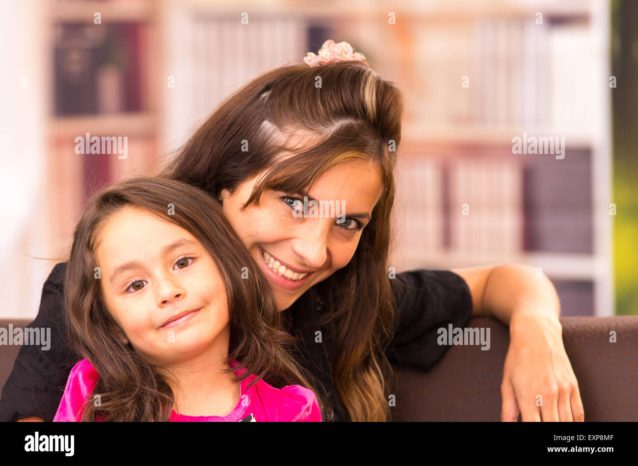 Mom and daughter posing happily indoors with heads tilted smiling - Stock Image