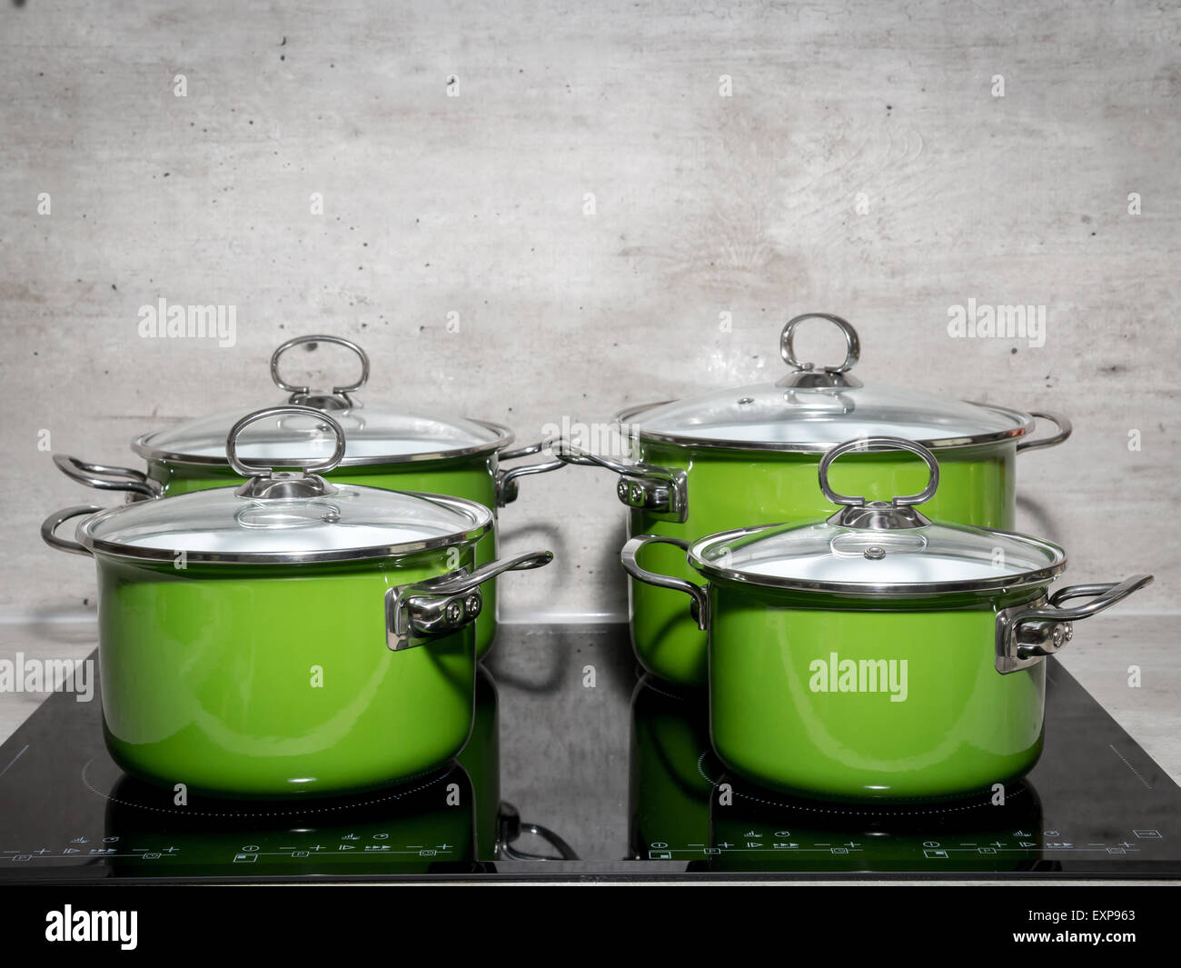 Four green enamel stewpots on black induction cooker - Stock Image