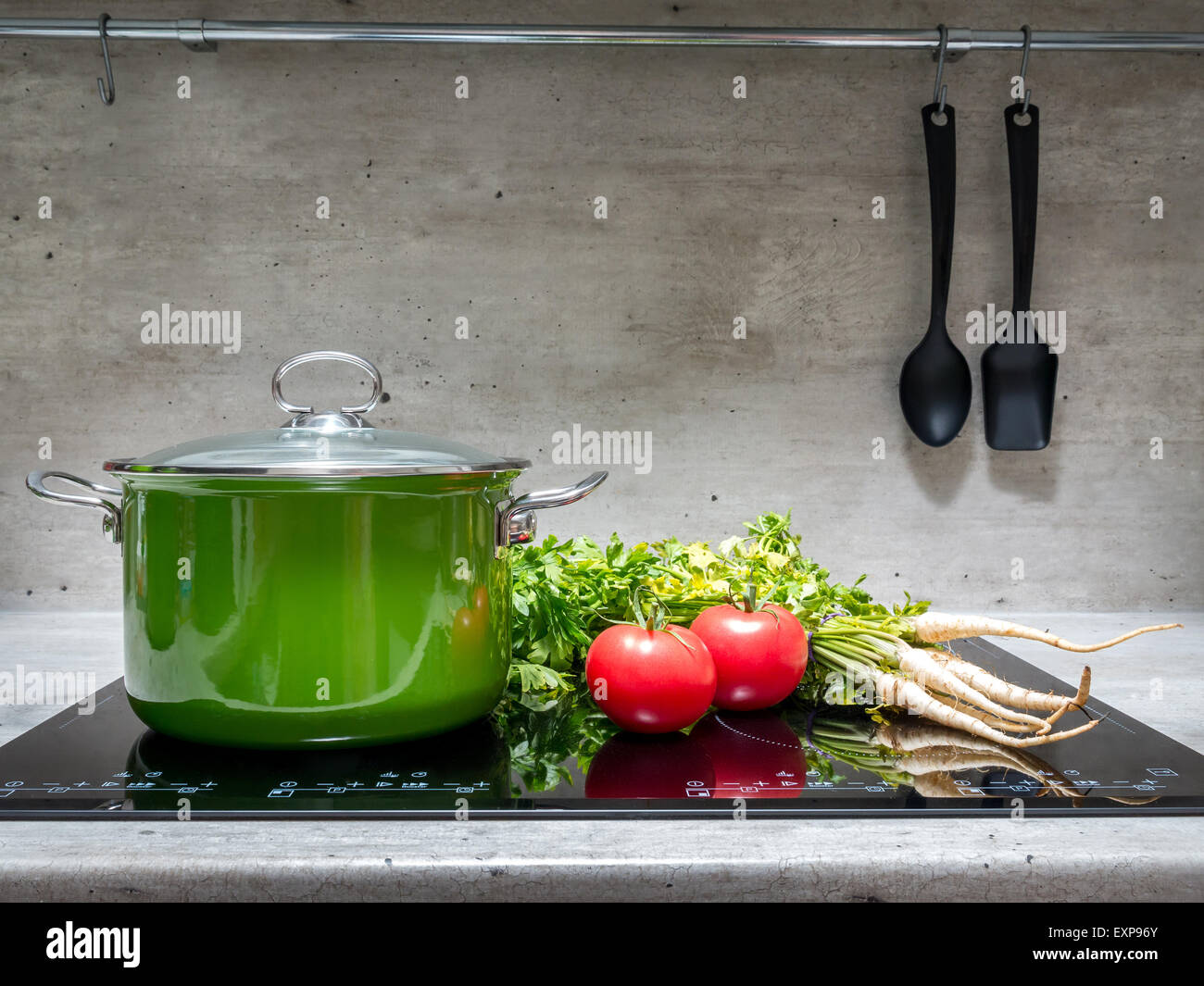Green enamel stewpot with parsley and two tomatoes on black induction cooker - Stock Image