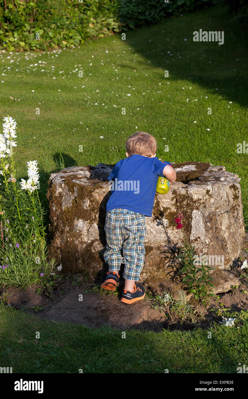 child looking into well,wishing well,danger,health and safety,awareness,protection, - Stock Image