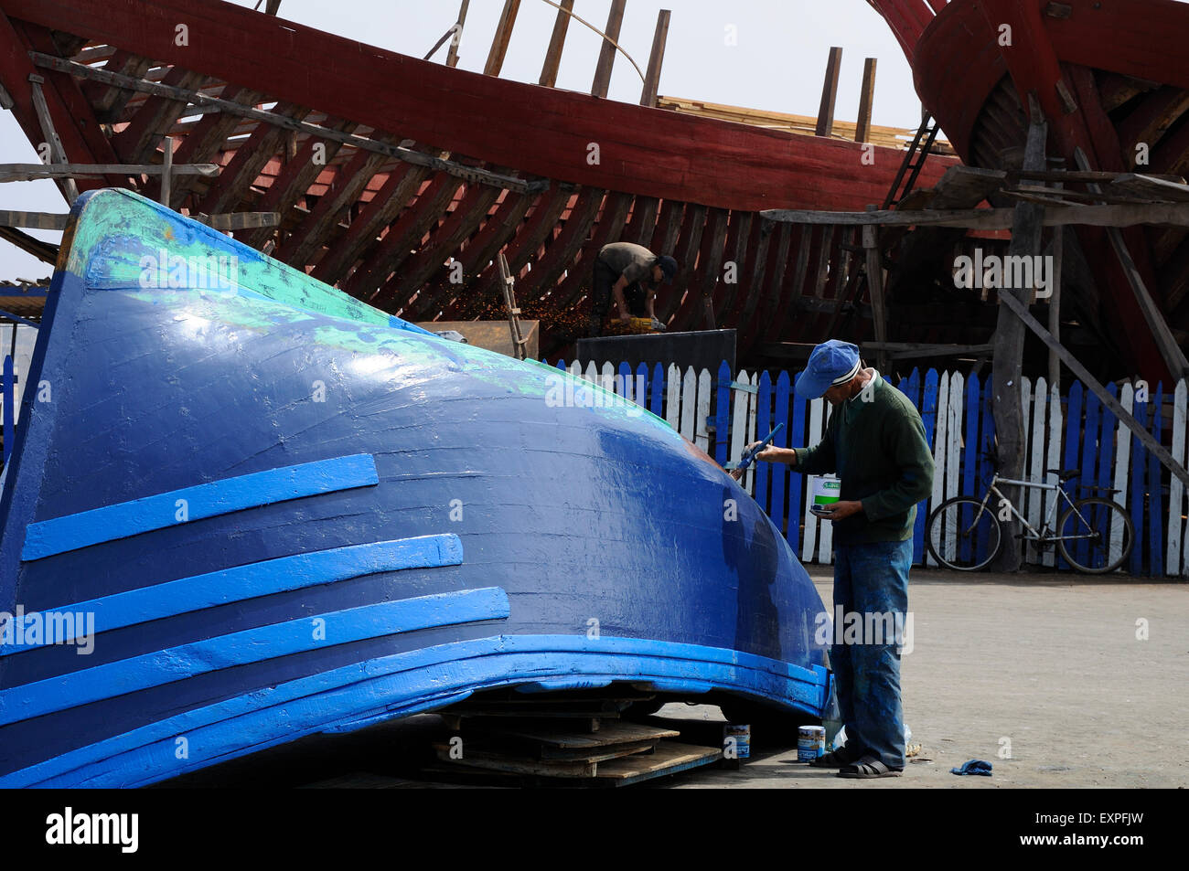 Man painting boat in Essaouira's shipyard. - Stock Image