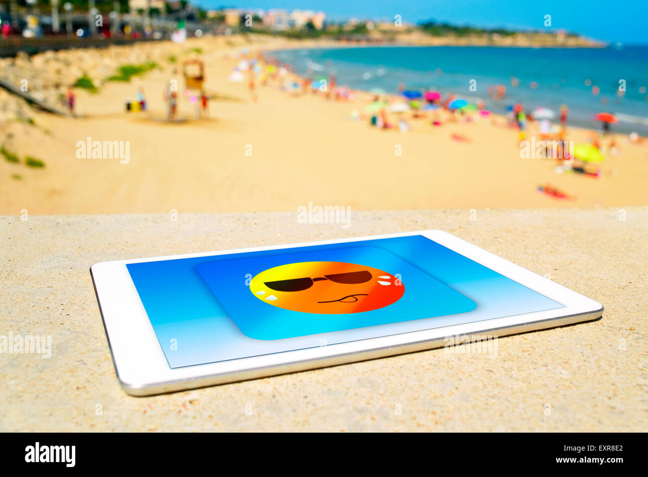 a tablet computer with an icon of a sun wearing sunglasses and sweating, designed by myself, at the beach, depicting - Stock Image