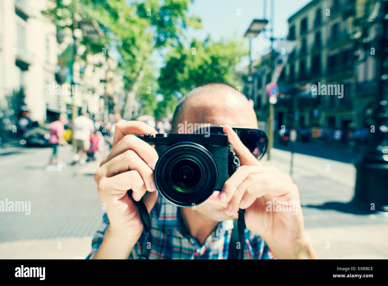 a young caucasian man wearing sunglasses points his camera to the observer at La Rambla in Barcelona, Spain - Stock Image