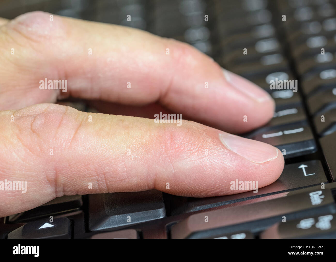 Man typing on a computer keyboard. - Stock Image