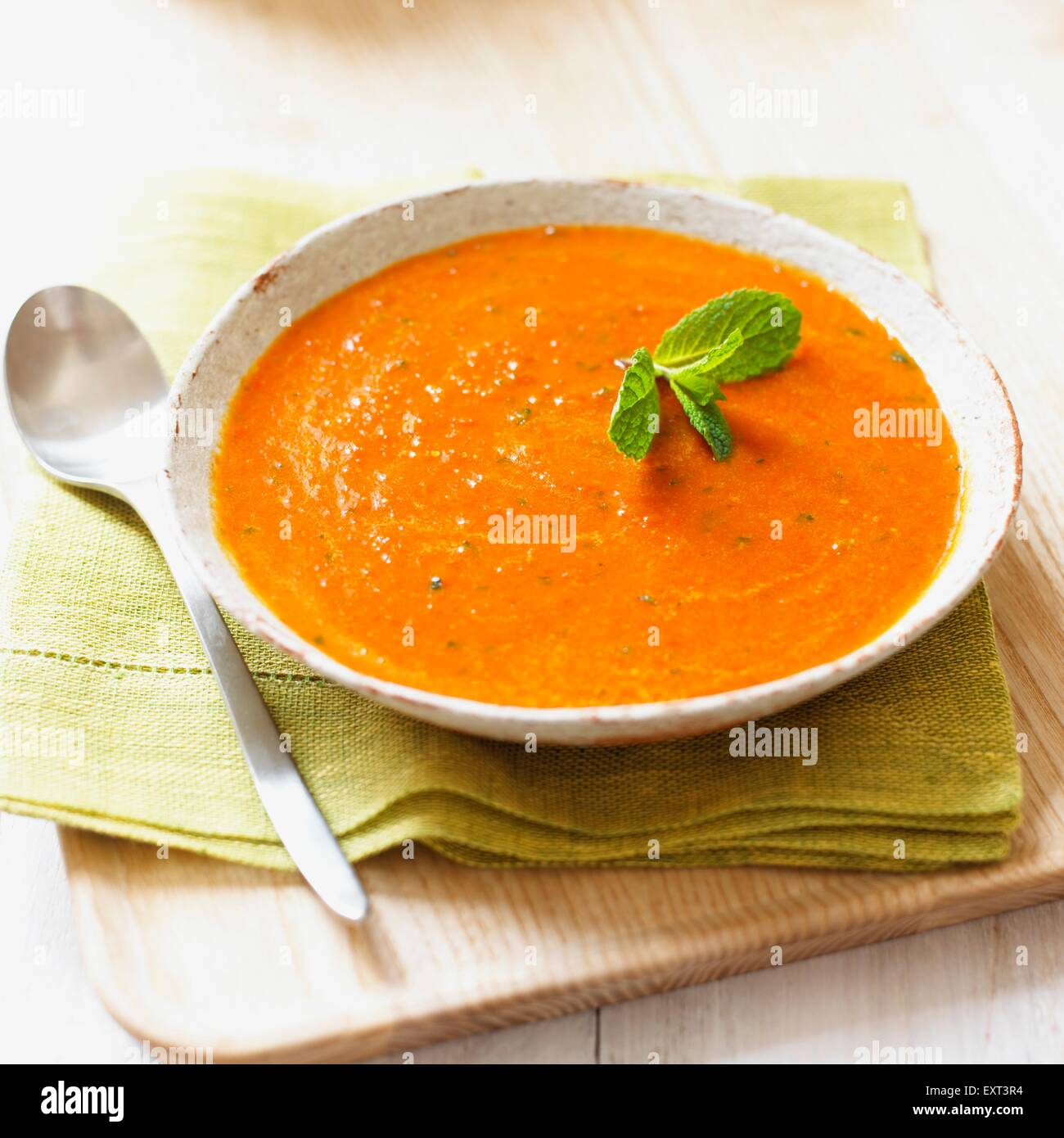 Bowl of goji berry and mint soup, with spoon and napkin - Stock Image