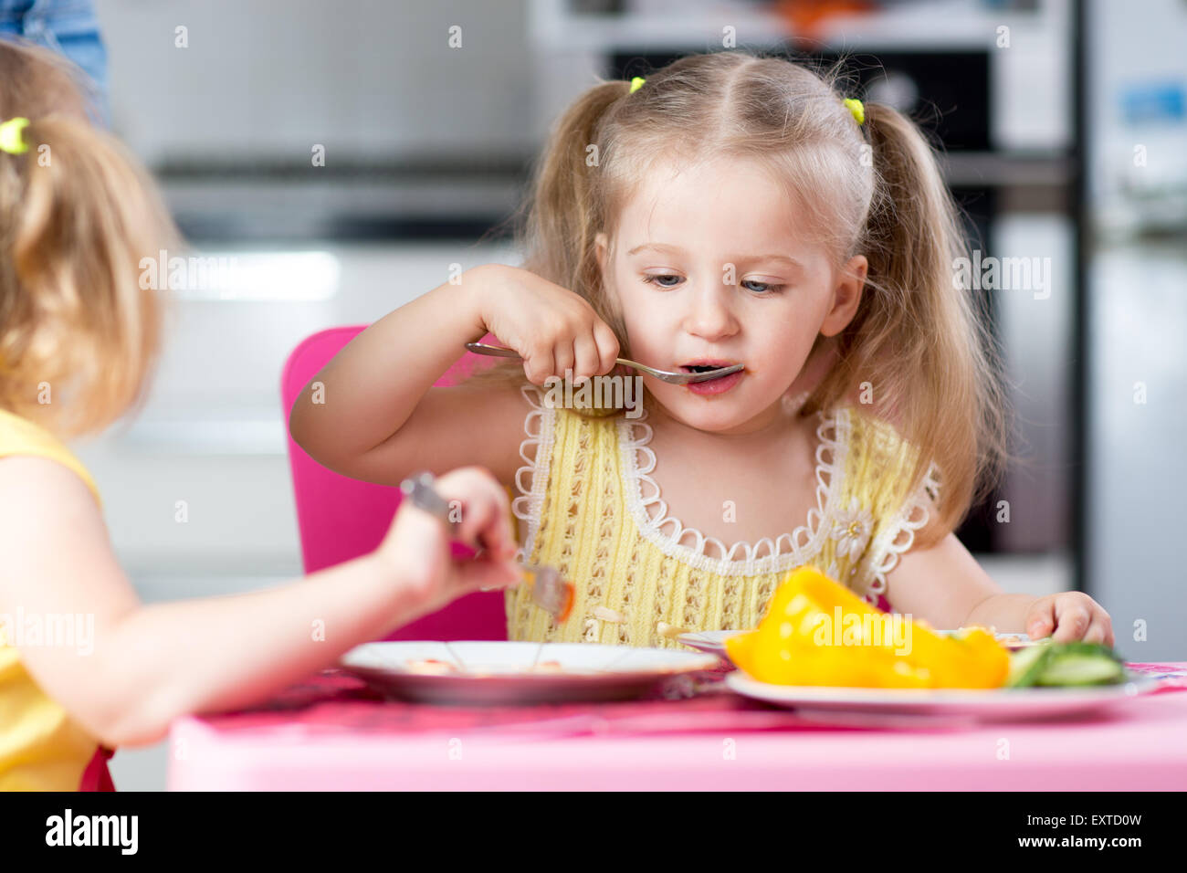 Little children eating food at daycare Stock Photo