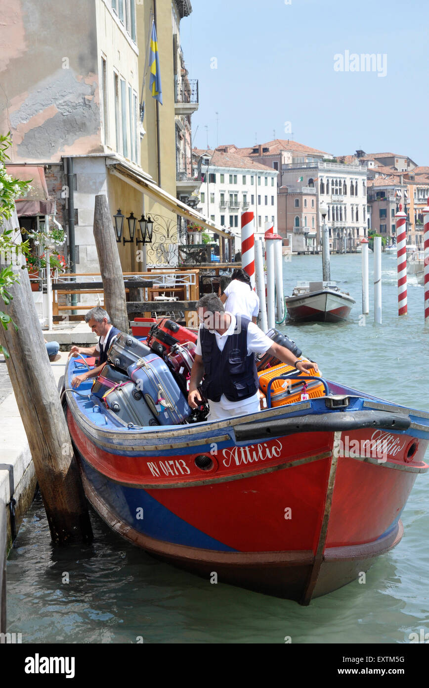 Italy Venice Cannaregio region - Canale Grande - hotel luggage arriving by work boat - porters loading - sunlight - Stock Image