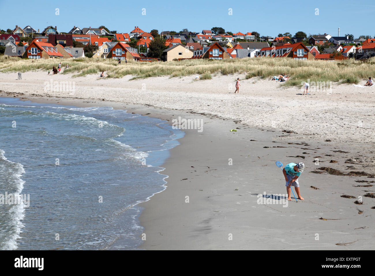 Surf at Hundested Beach on a summer's day. Boy drawing in the sand with a stick. - Stock Image