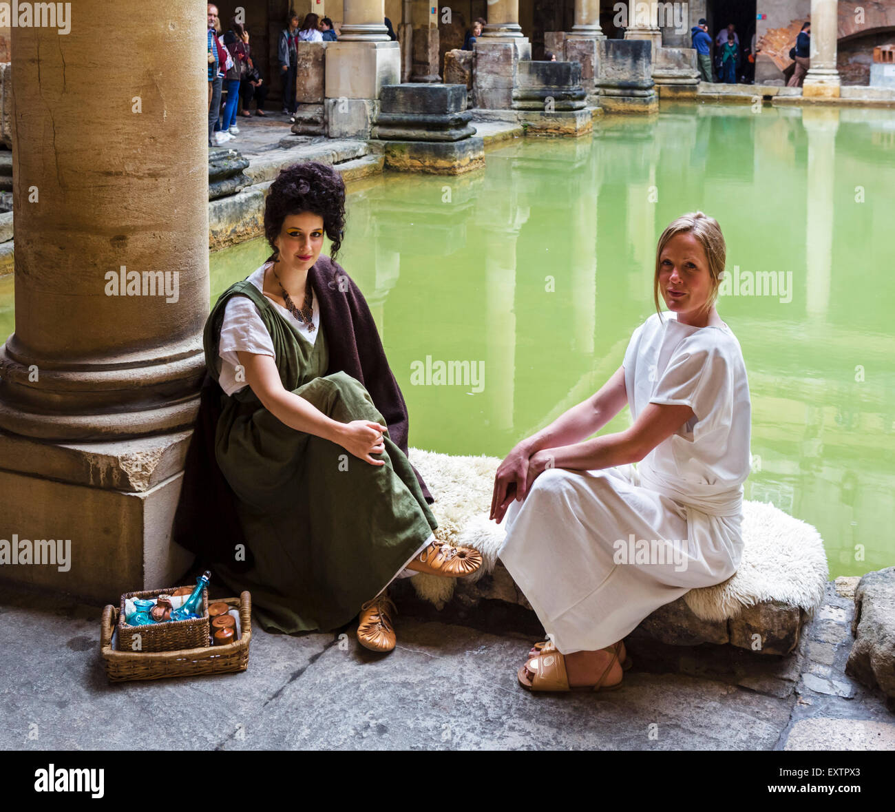 Re-enactors wearing Roman costume by the Great Bath at the Roman Baths in Bath, Somerset, England, UK - Stock Image