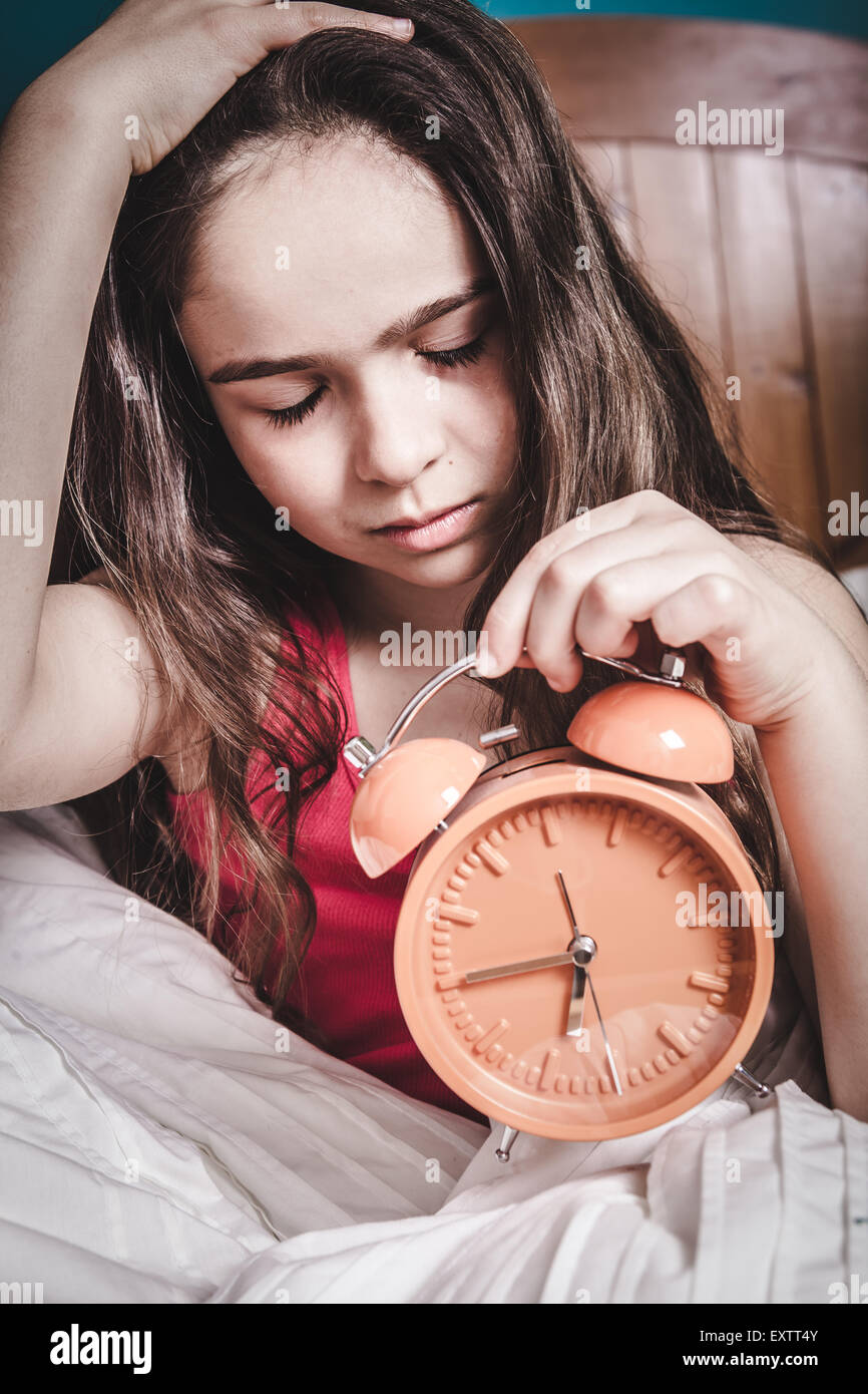 Teen sleepy young girl waking up in bed