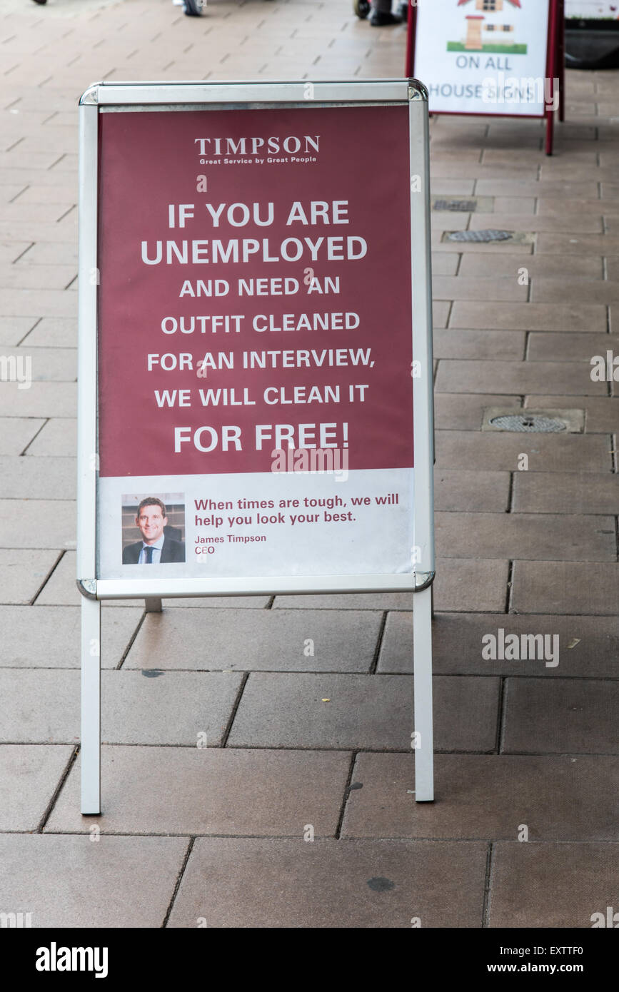 Sign outside a Timpsons store in Exmouth Devon indicating that they will dry clean an outfit for an unemployed person - Stock Image
