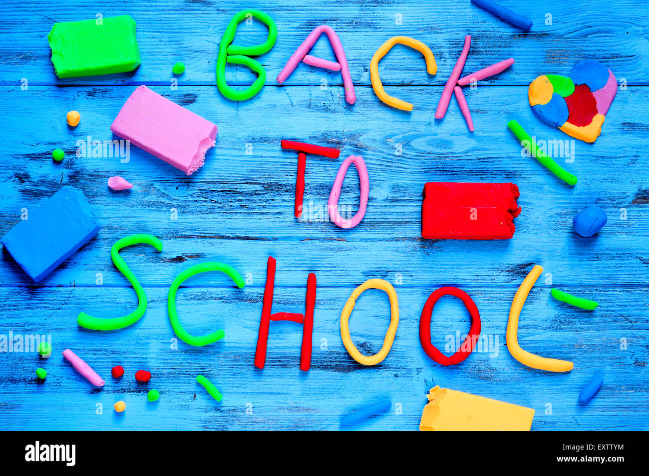 the sentence back to school written with modelling clay of different colors on a blue rustic wooden background - Stock Image
