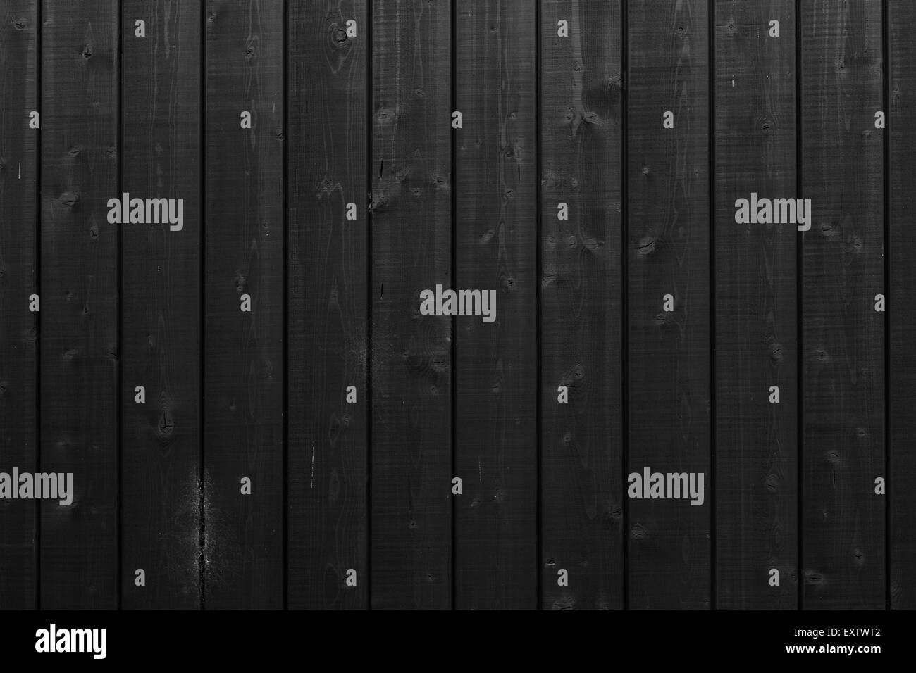 background that consists of vertical black planks on wooden part of building - Stock Image