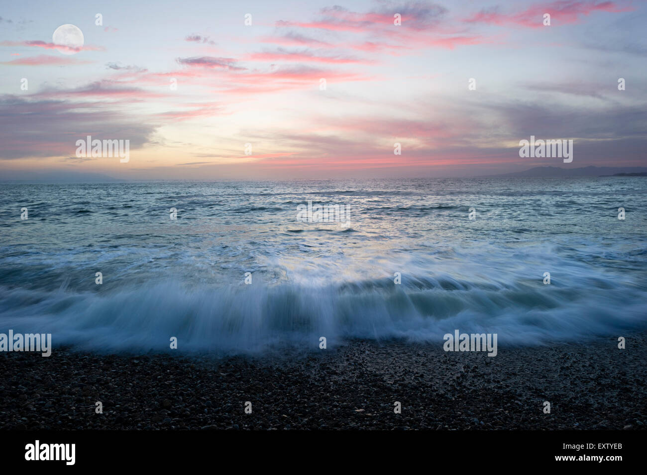 Ocean landscape with waves breaking on beach and moon clouds. Stock Photo