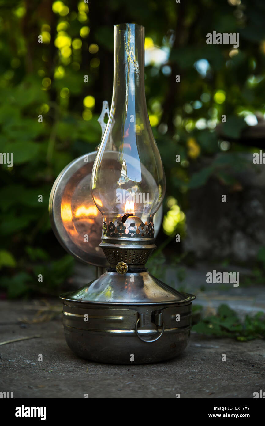 old kerosene lamp stands on the ground, outdoors - Stock Image