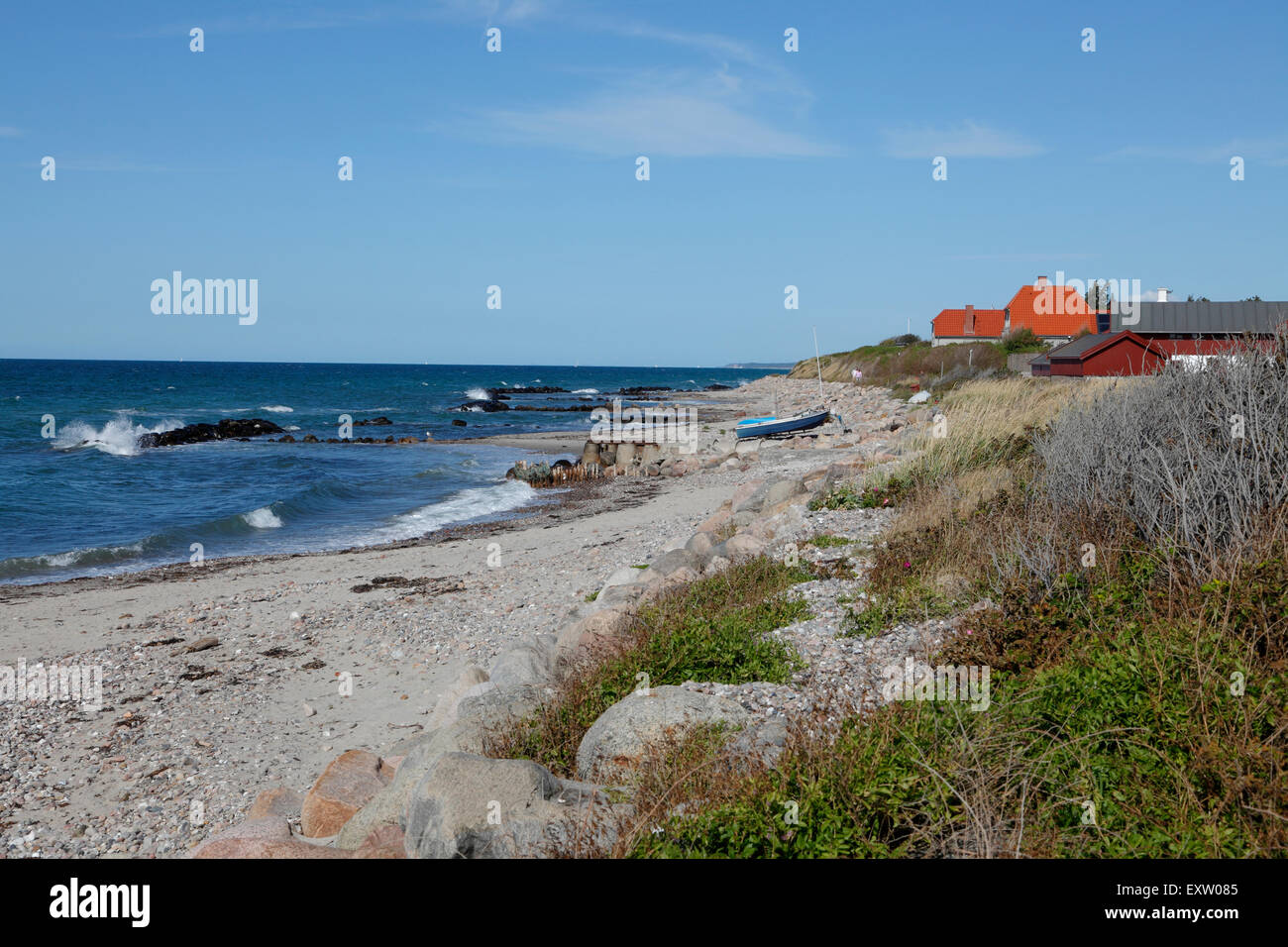 Viewing east along the rough coast of the fishing hamlet Kikhavn near Hundested on a sunny summer's day. - Stock Image