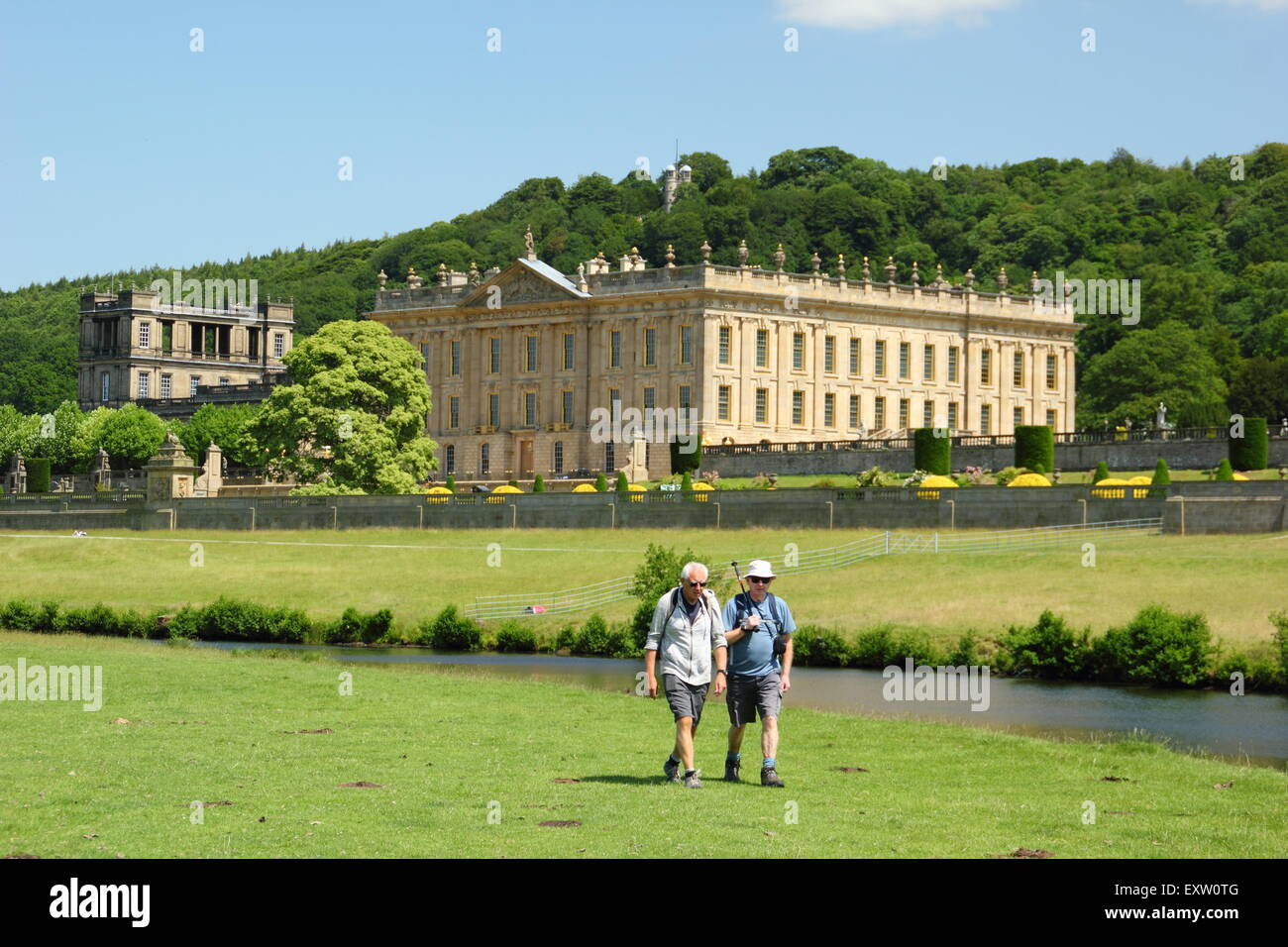 Two men walk on the banks of the River Derwent by Chatsworth House in the Peak District on a glorious summer day, - Stock Image