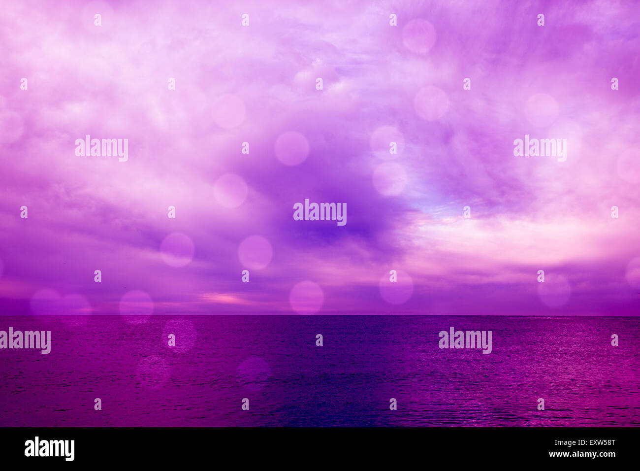 Dramatic seascape in magenta with light bokeh - Stock Image