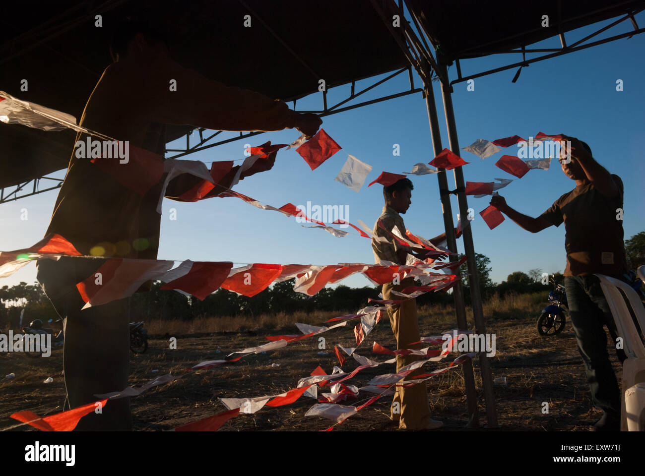 People hanging out Indonesian small flags for local event. - Stock Image