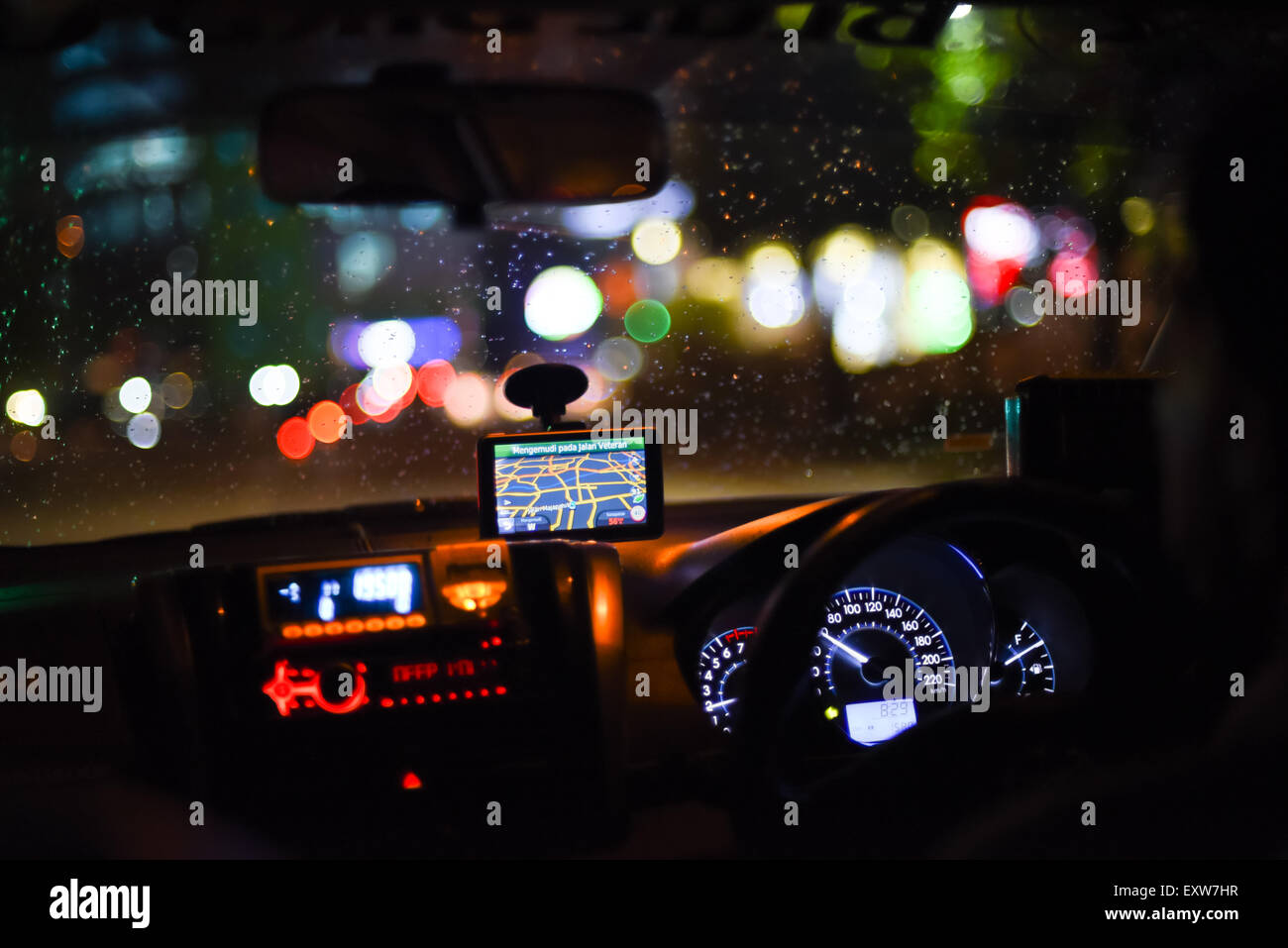 Taxi dashboard and interiors during night trip in Jakarta, Indonesia. - Stock Image