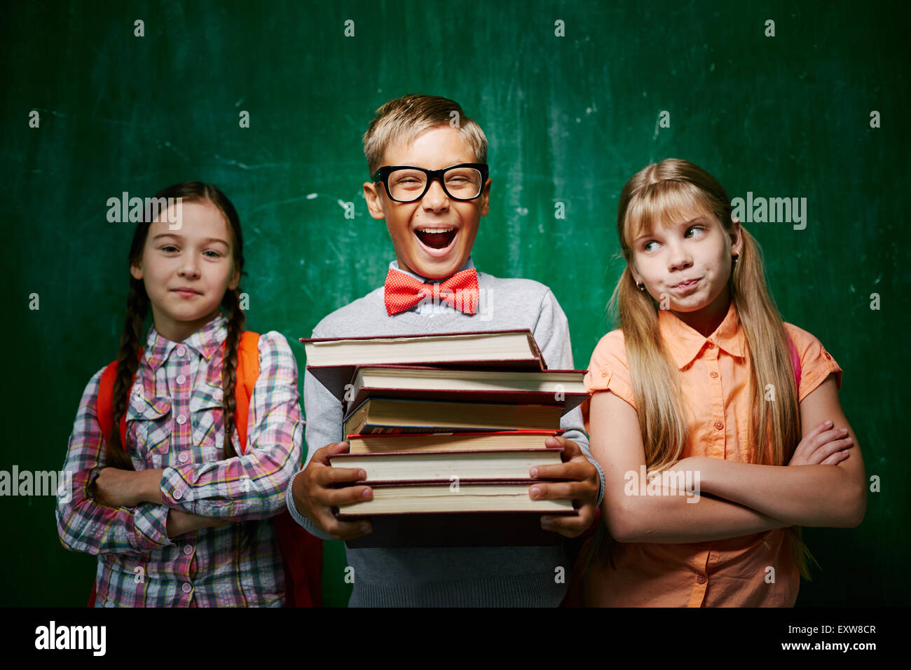 Ecstatic pupil with books standing between two schoolmates - Stock Image
