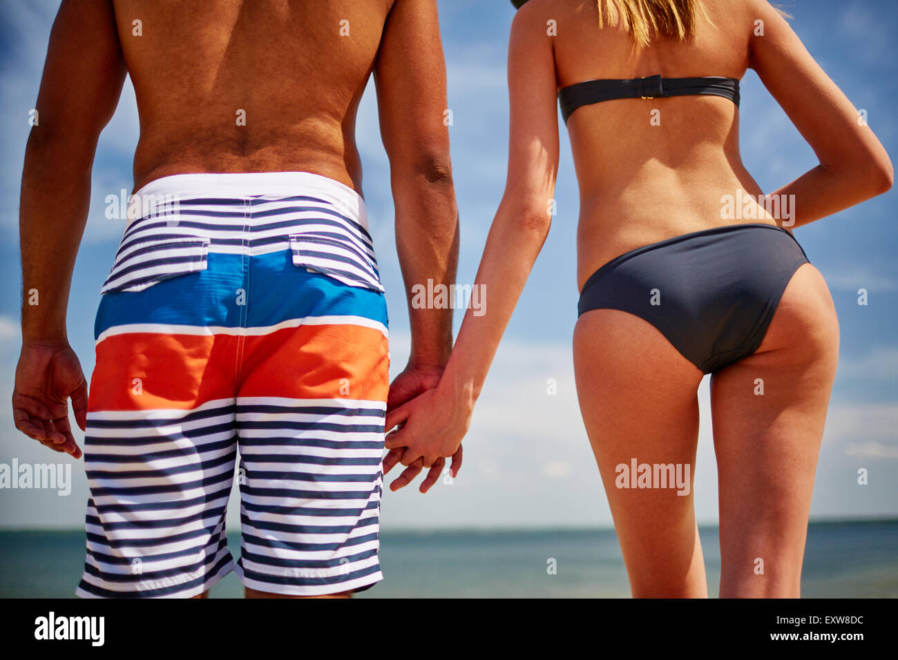 Rear view of couple in swimwear at the seaside - Stock Image