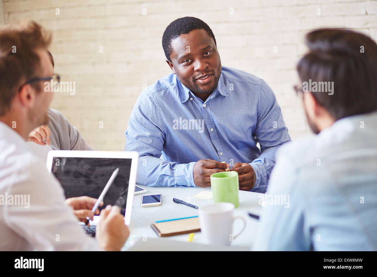 Serious manager of African ethnicity talking to colleagues - Stock Image