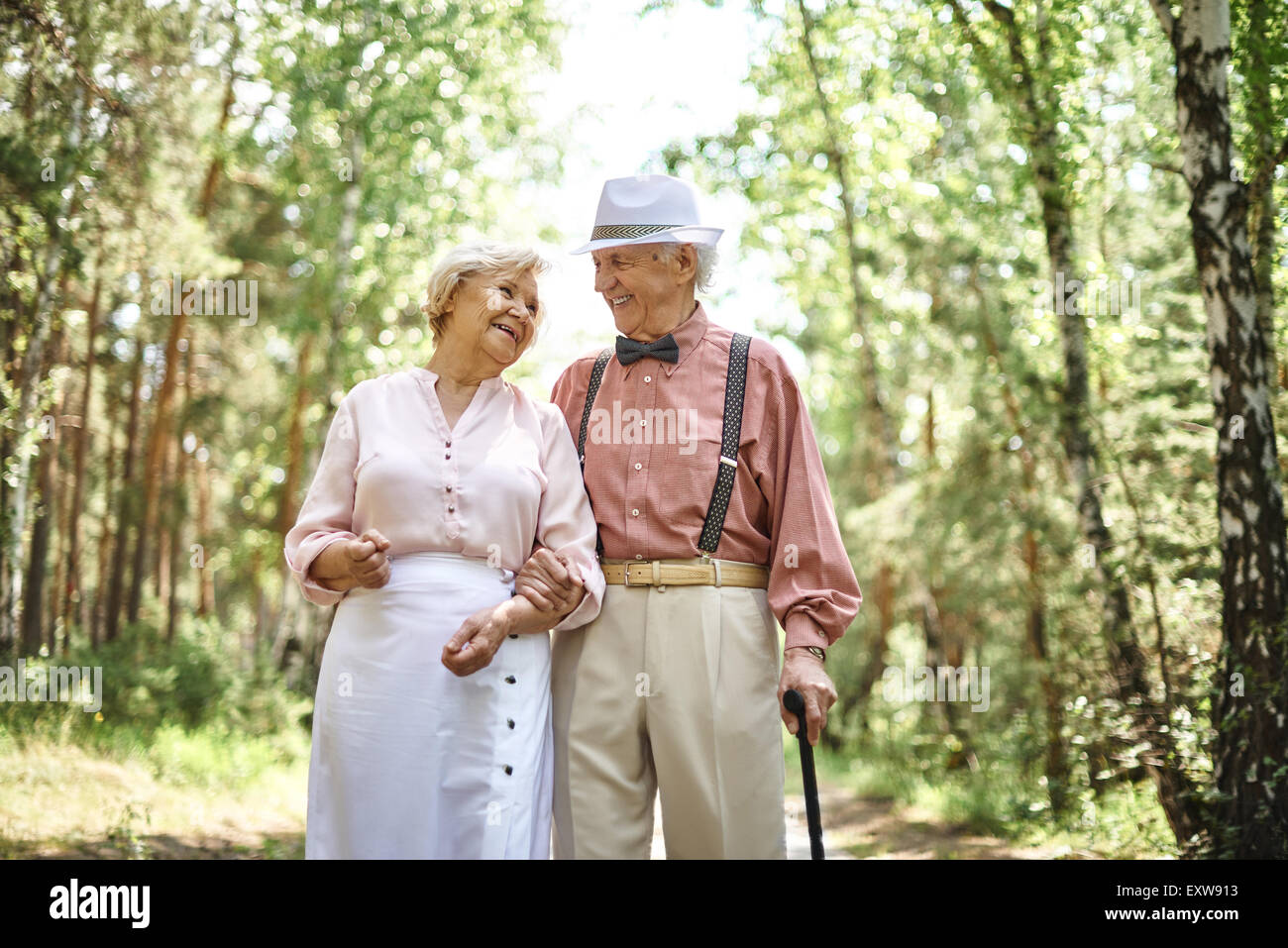 Affectionate seniors in smart casual talking while chilling out in park - Stock Image
