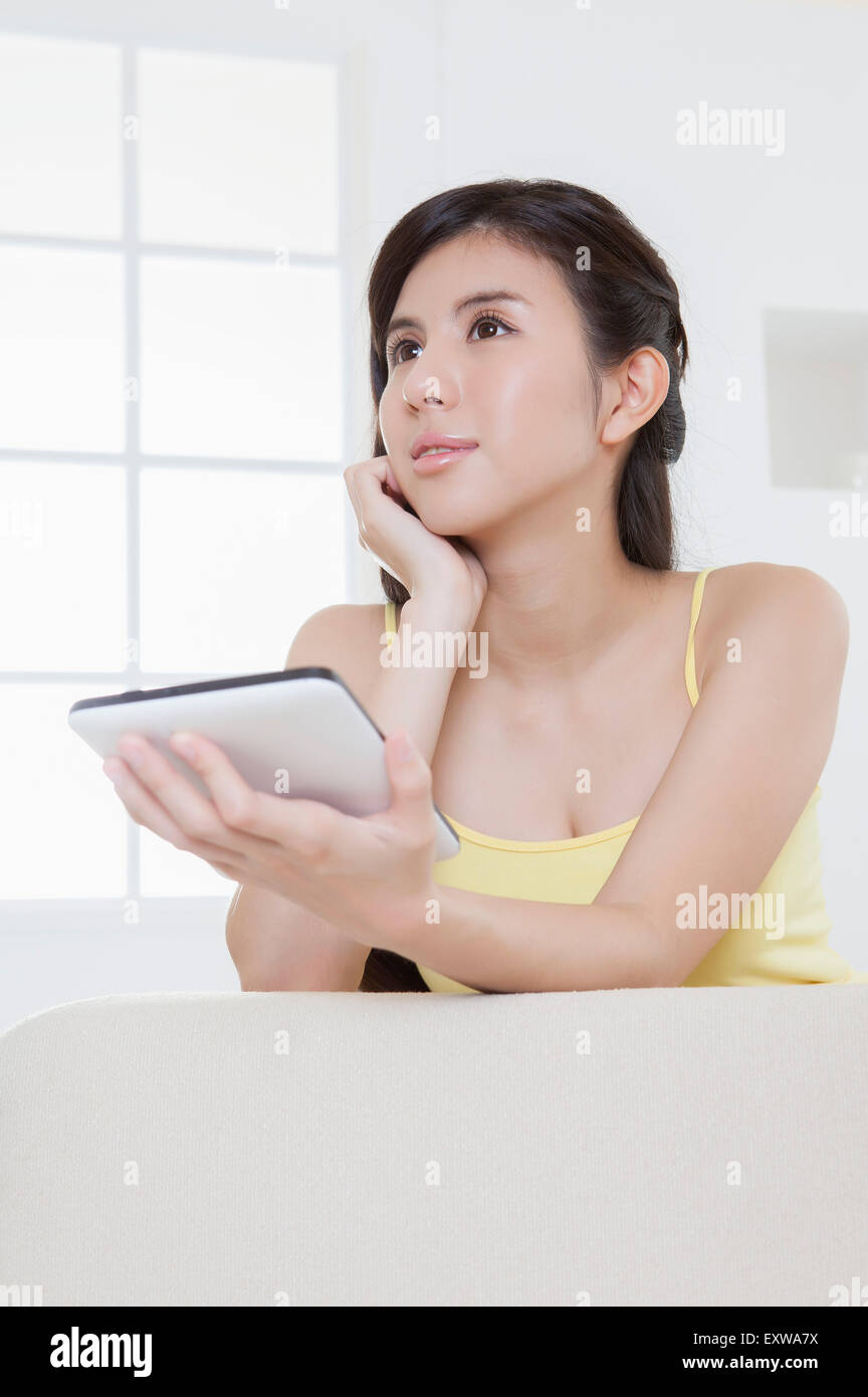 Young woman holding touch pad and looking away, - Stock Image
