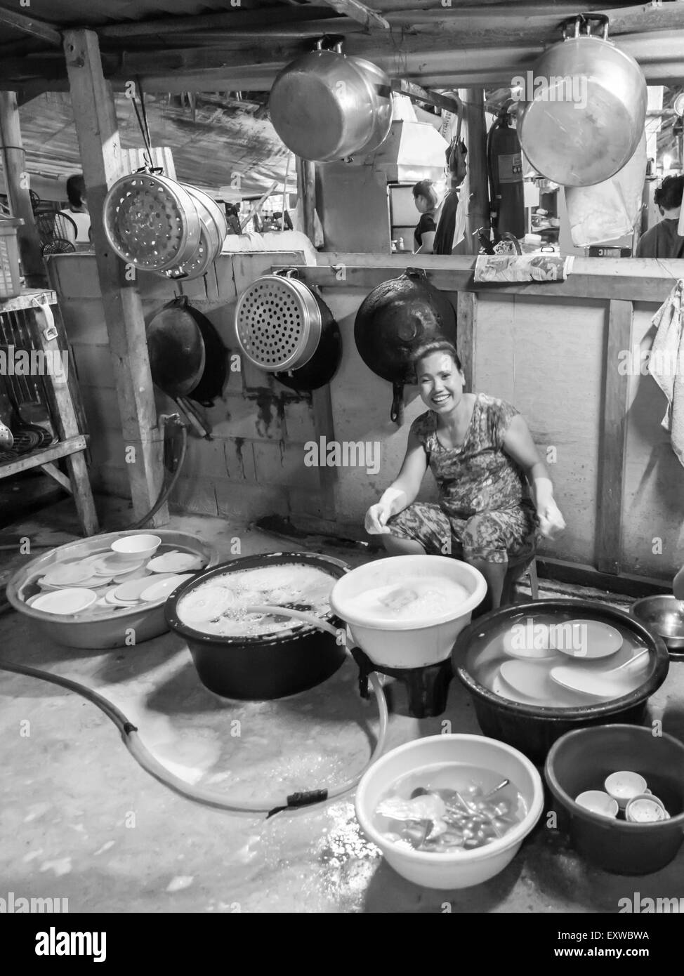 Thai woman washing dishes and pots, traditional restaurant, Kanchanaburi Province, Central Thailand, Thailand - Stock Image