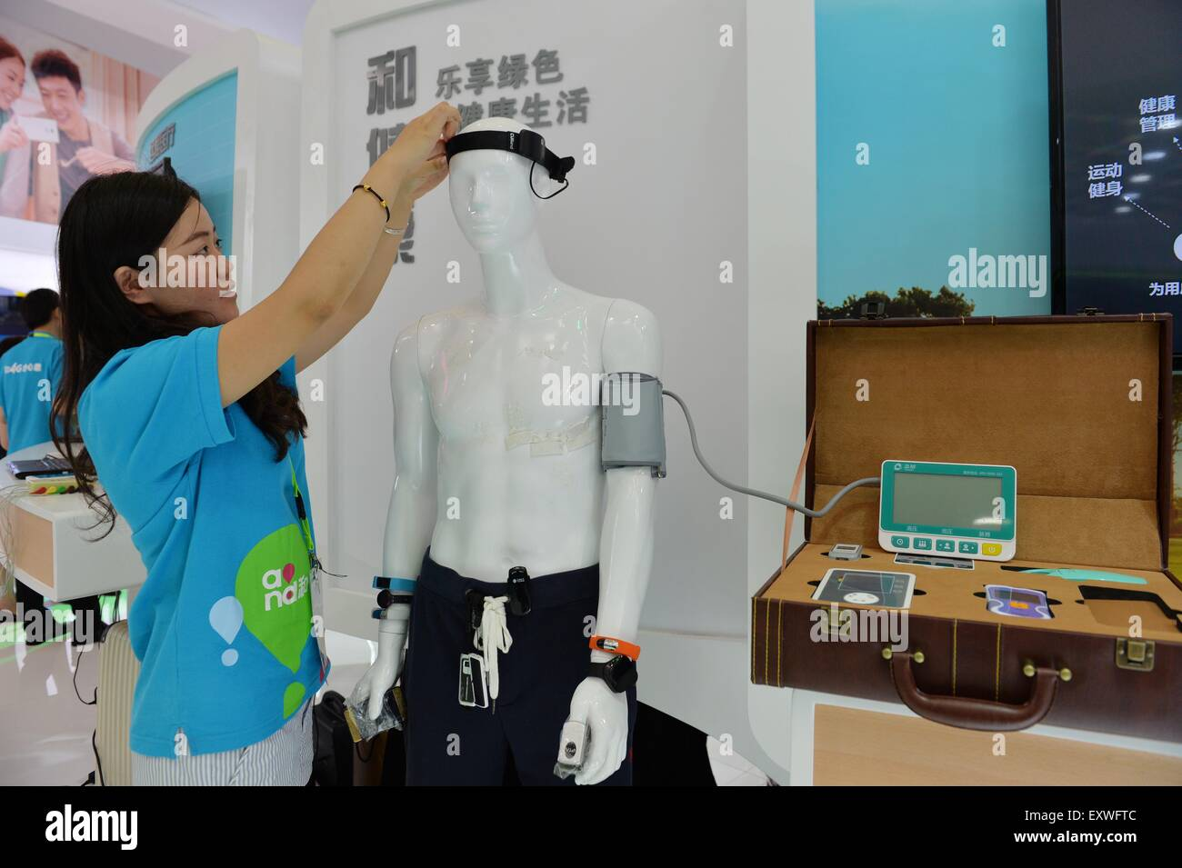 Shanghai, China. 17th July, 2015. An exhibitor adjusts a brainwave instrument during the Mobile World Congress Shanghai Stock Photo