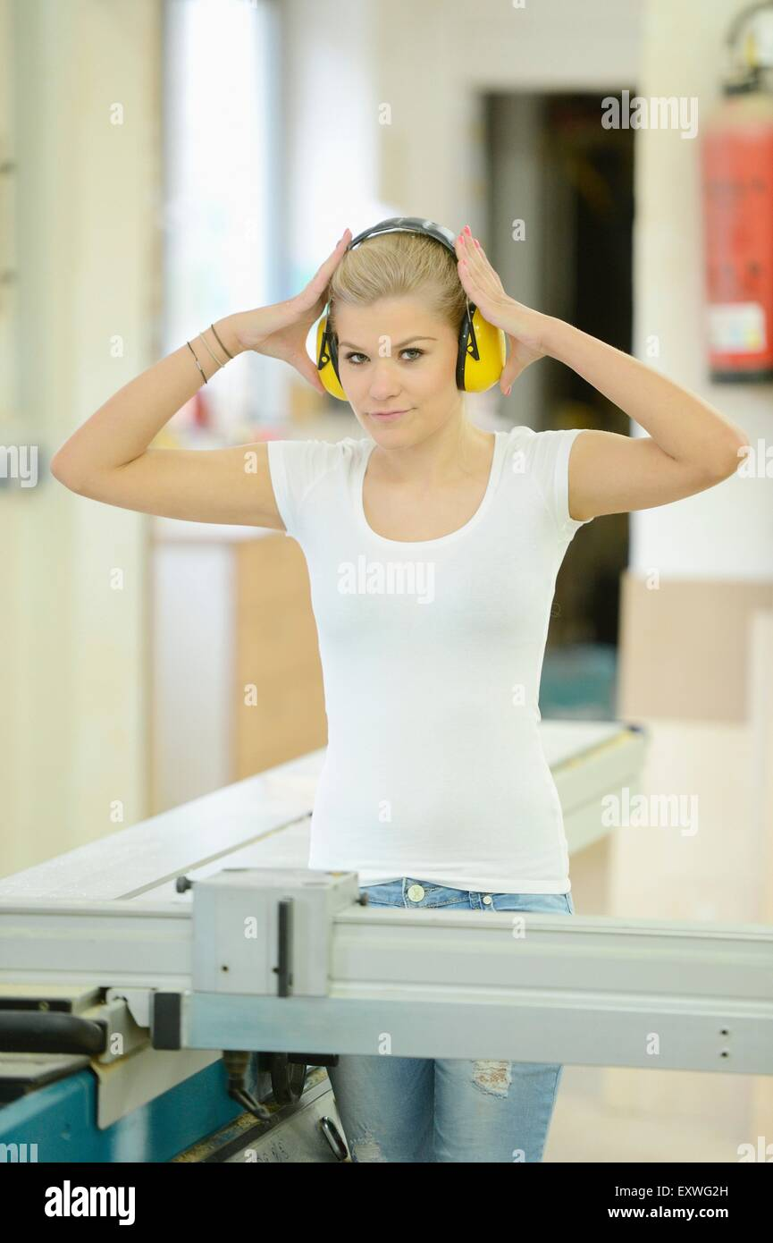 Young woman working in a carpentry on a buzzsaw Stock Photo