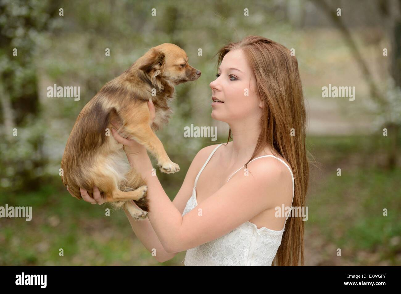 Young woman with a mixed breed dog puppy in garden Stock Photo