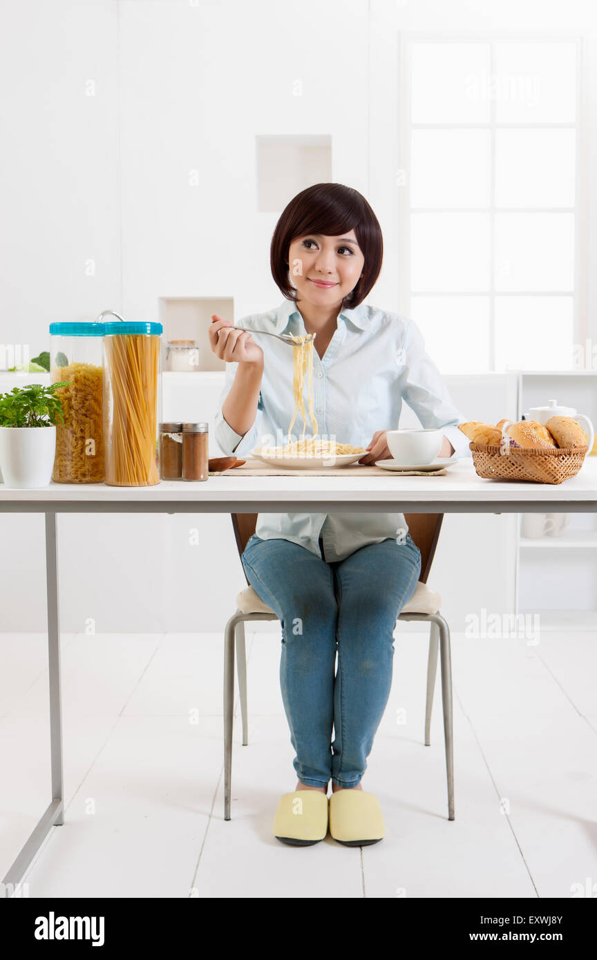 Young woman eating noodles and looking up with smile, - Stock Image