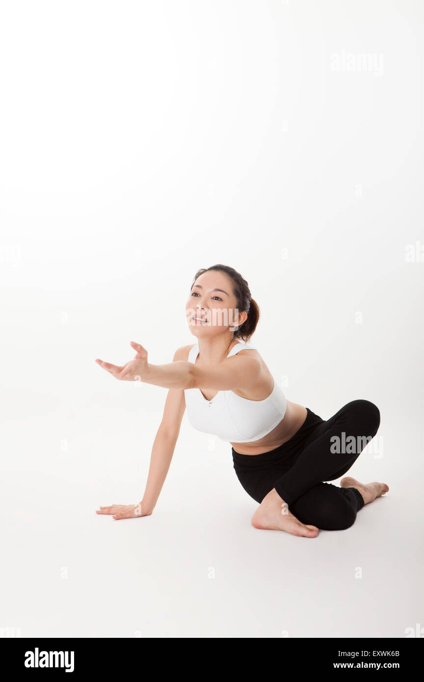 Woman practicing yoga and reaching one hand out, - Stock Image