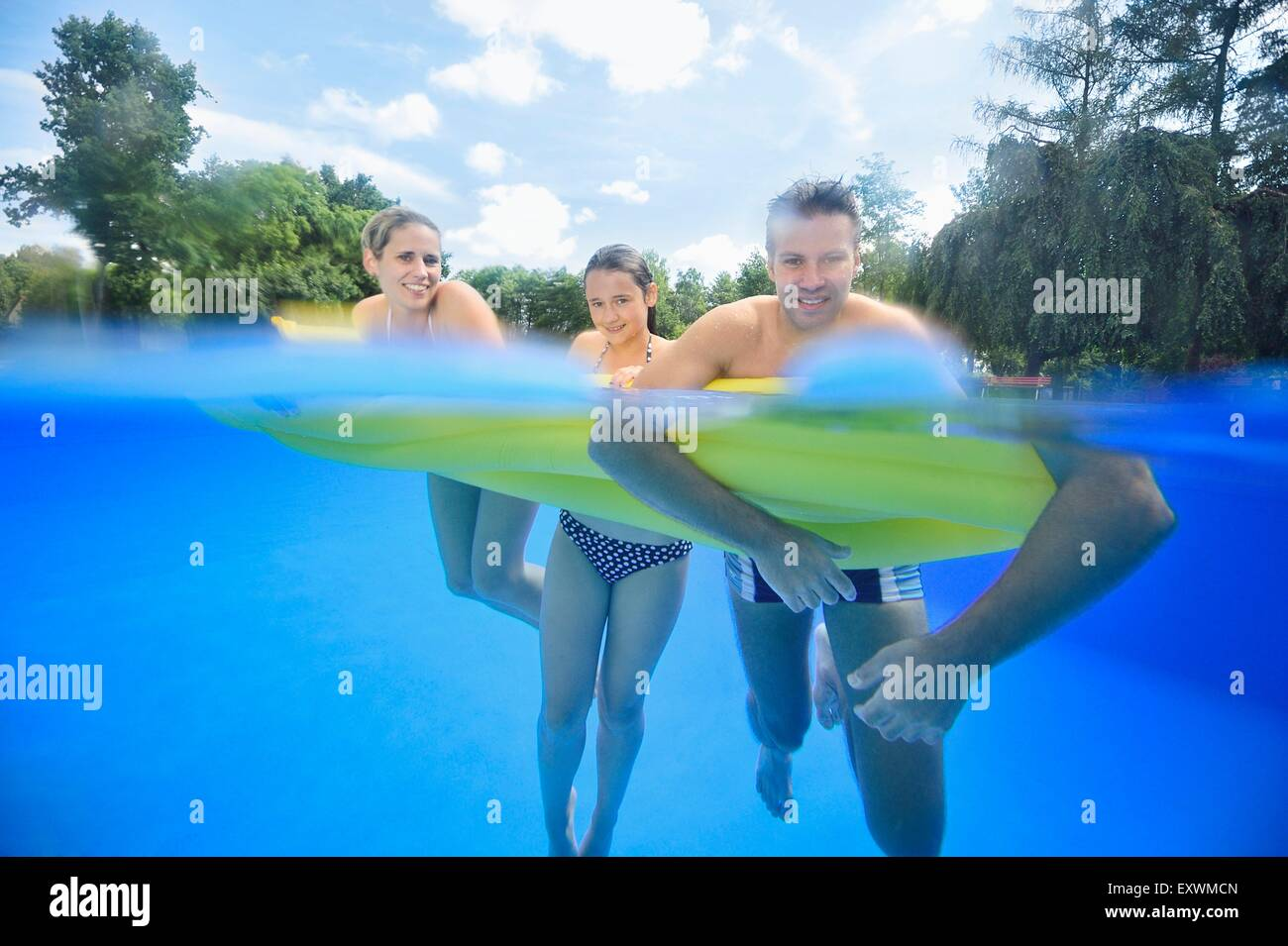Happy family in an open-air bath - Stock Image