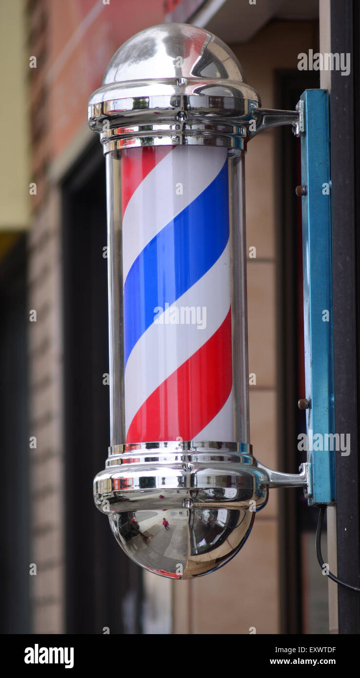 American barber pole sign with a helical stripe (red, white, and blue ) on a wall of a Barber's shop. - Stock Image