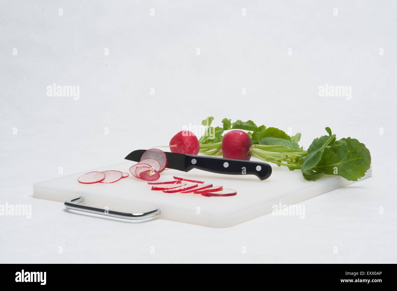 Chopping board with kitchen knife and radish - Stock Image