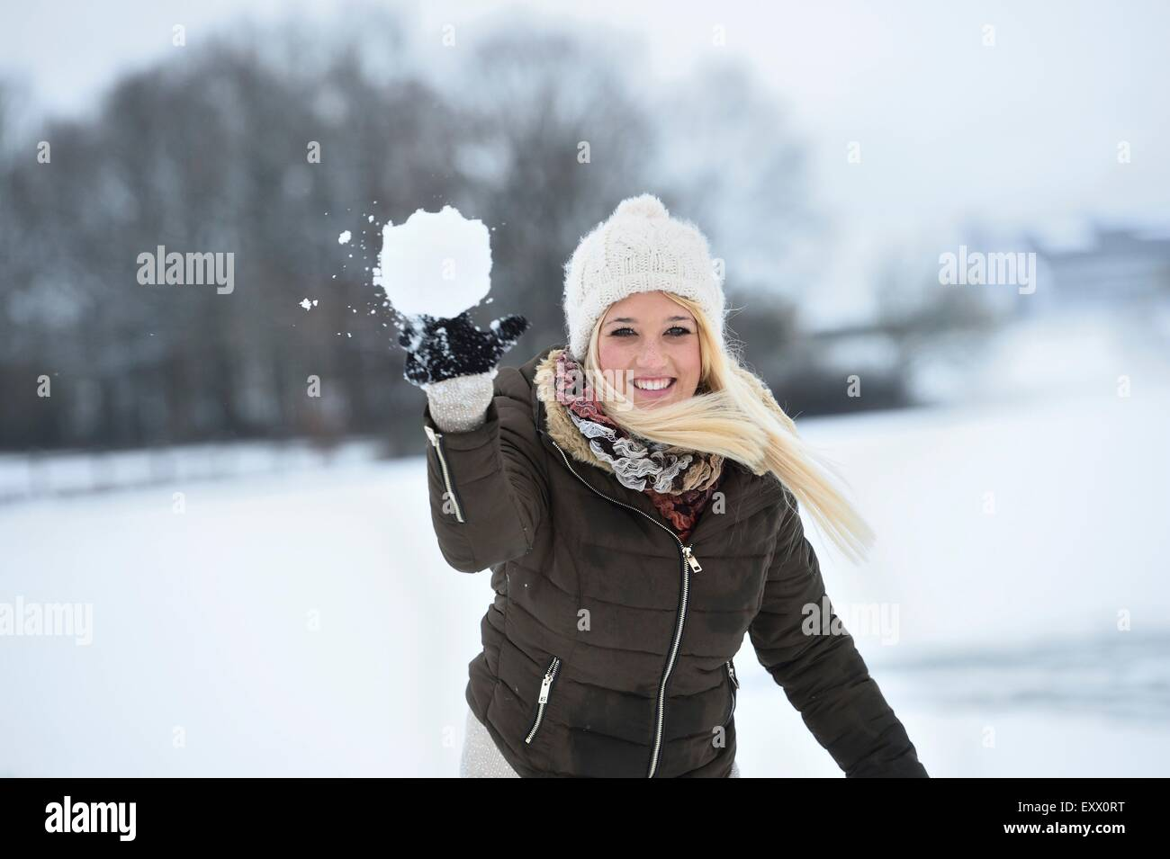 Happy young woman throwing a snowball - Stock Image