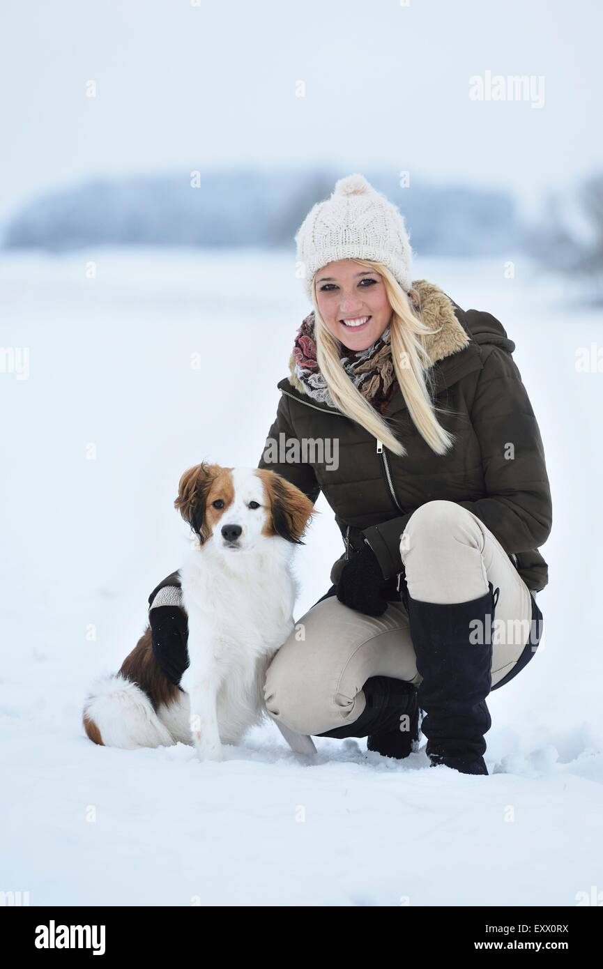 Young woman with a Kooikerhondje dog in snow - Stock Image